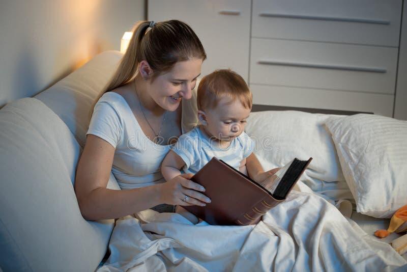 Κινηματογράφηση σε πρώτο πλάνο της όμορφης ιστορίας αφήγησης μητέρων χαμόγελου στο μωρό της στοκ φωτογραφία
