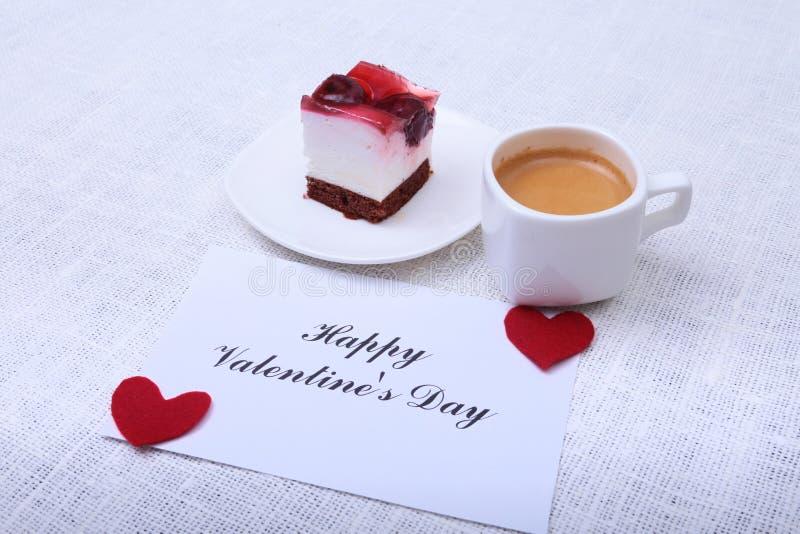 Κινηματογράφηση σε πρώτο πλάνο του άσπρου κέικ φλιτζανιών του καφέ και φραουλών Κόκκινη ημέρα βαλεντίνων καρδιών στοκ φωτογραφία με δικαίωμα ελεύθερης χρήσης