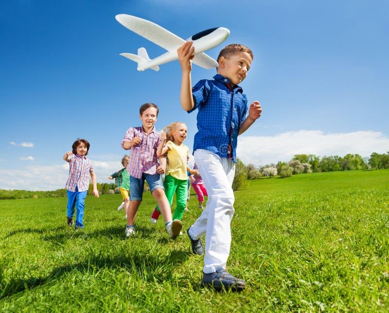 Κινηματογράφηση σε πρώτο πλάνο του αεροπλάνου και των παιδιών εκμετάλλευσης αγοριών πίσω στοκ εικόνες