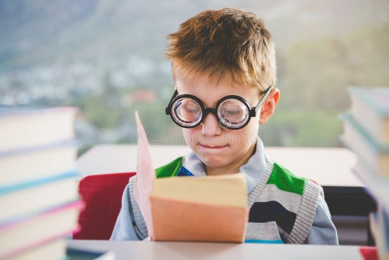 Κινηματογράφηση σε πρώτο πλάνο του βιβλίου ανάγνωσης schoolkid στην τάξη στοκ εικόνες