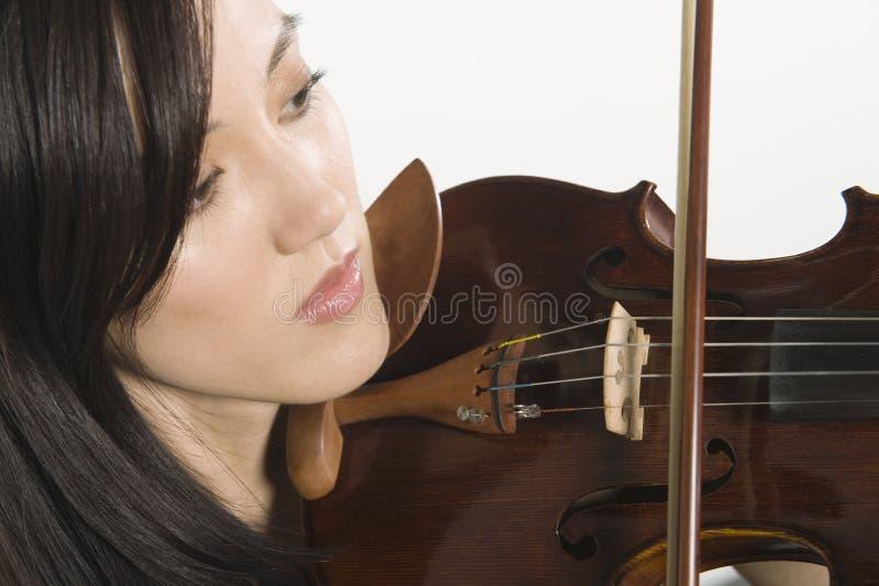 Κινηματογράφηση σε πρώτο πλάνο του βιολιού παιχνιδιού γυναικών στοκ φωτογραφία