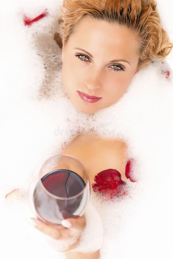 Κινηματογράφηση σε πρώτο πλάνο του εμπαθούς χαλαρώνοντας αισθησιακού καυκάσιου ξανθού θηλυκού στη Foamy μπανιέρα στοκ φωτογραφία