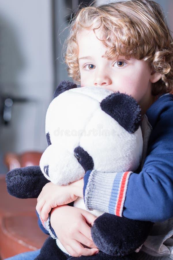 Κινηματογράφηση σε πρώτο πλάνο του καλού ξανθού αγοριού με τη σγουρή τρίχα που αγκαλιάζει το παιχνίδι panda στοκ εικόνα με δικαίωμα ελεύθερης χρήσης
