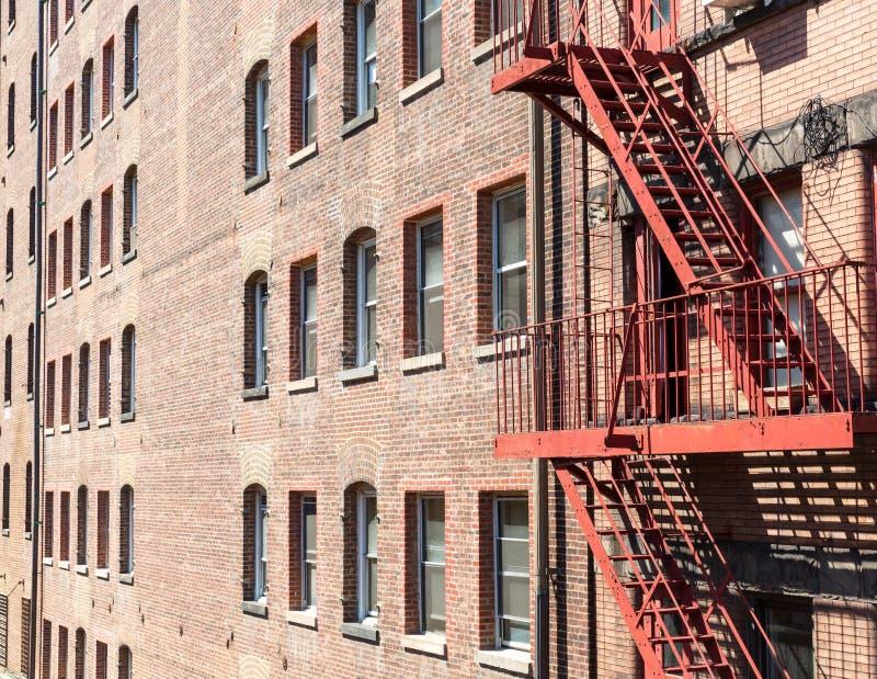 Κινηματογράφηση σε πρώτο πλάνο του κτηρίου τούβλου με τις σκάλες πυρκαγιάς στοκ εικόνες με δικαίωμα ελεύθερης χρήσης