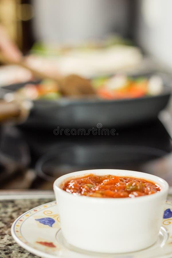 Κινηματογράφηση σε πρώτο πλάνο του κύπελλου της καυτής σάλτσας που προετοιμάζεται για μεξικάνικα τρόφιμα στοκ εικόνα