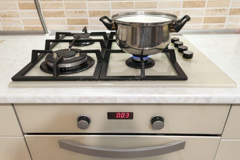 Κινηματογράφηση σε πρώτο πλάνο του μαγειρεύοντας δοχείου ανοξείδωτου στη σόμπα αερίου στο contempo στοκ εικόνα