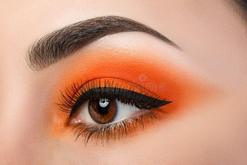 Κινηματογράφηση σε πρώτο πλάνο του ματιού γυναικών με τα όμορφα πορτοκαλιά μάτια smokey στοκ φωτογραφία