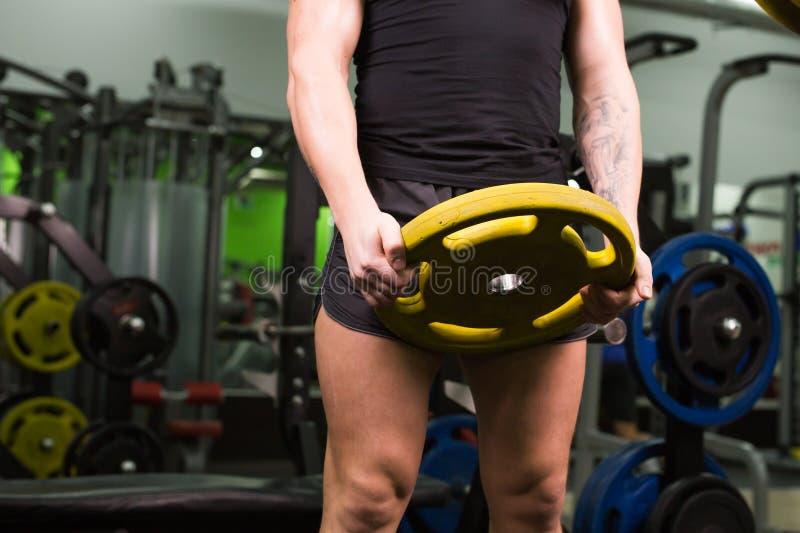 Κινηματογράφηση σε πρώτο πλάνο του νέου υγιούς άνδρα με τους μεγάλους μυς που κρατά τα βάρη δίσκων στη γυμναστική Ικανότητα, αθλη στοκ εικόνες