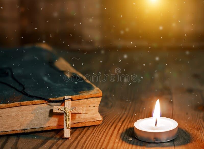Κινηματογράφηση σε πρώτο πλάνο του ξύλινου χριστιανικού σταυρού στη Βίβλο, καίγοντας κερί στον παλαιό πίνακα στοκ φωτογραφία με δικαίωμα ελεύθερης χρήσης