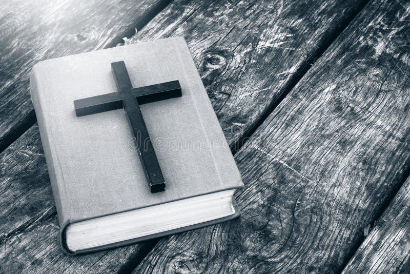 Κινηματογράφηση σε πρώτο πλάνο του ξύλινου χριστιανικού σταυρού στη Βίβλο στον παλαιό πίνακα στοκ φωτογραφίες
