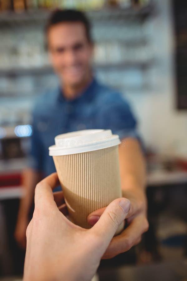 Κινηματογράφηση σε πρώτο πλάνο του πελάτη που παίρνει τον καφέ από το barista στον καφέ στοκ φωτογραφίες με δικαίωμα ελεύθερης χρήσης
