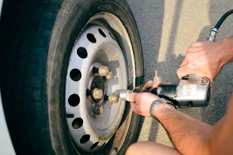 Κινηματογράφηση σε πρώτο πλάνο του προσώπου που ελέγχει τα μπουλόνια καθορισμού στη ρόδα οχημάτων με τα γυμνά χέρια στοκ φωτογραφία με δικαίωμα ελεύθερης χρήσης