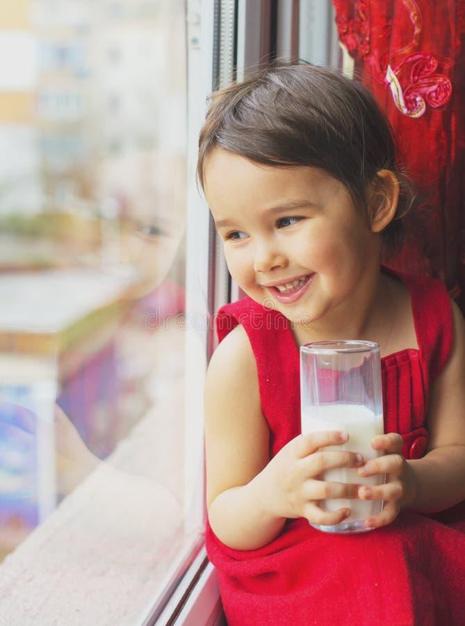 Κινηματογράφηση σε πρώτο πλάνο του πόσιμου γάλακτος μικρών κοριτσιών στοκ φωτογραφία