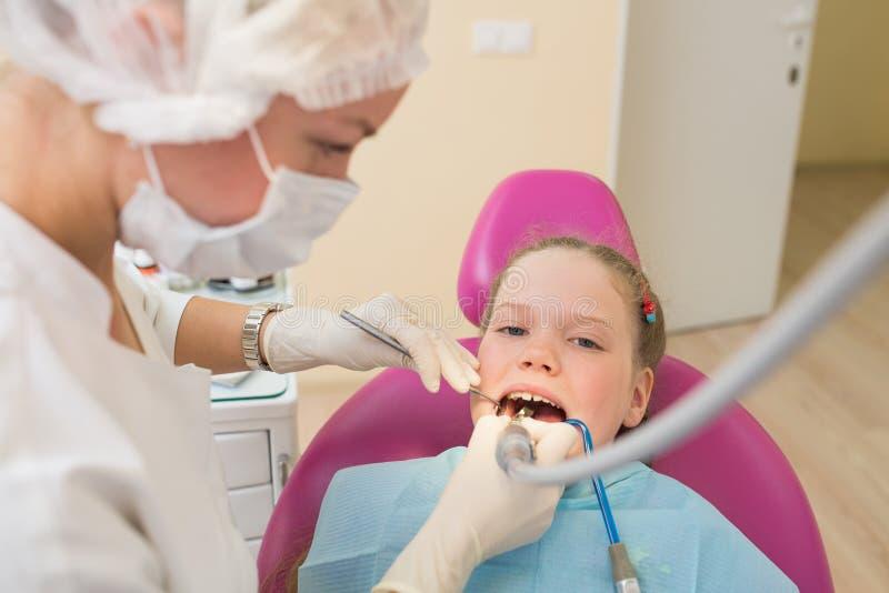 Κινηματογράφηση σε πρώτο πλάνο του στόματος ανοίγματος μικρών κοριτσιών ευρέως κατά τη διάρκεια της οδοντικής επεξεργασίας της στ στοκ φωτογραφία
