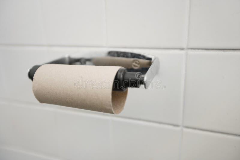 Κινηματογράφηση σε πρώτο πλάνο του τελειωμένου ρόλου χαρτιού τουαλέτας στο λουτρό στοκ εικόνα