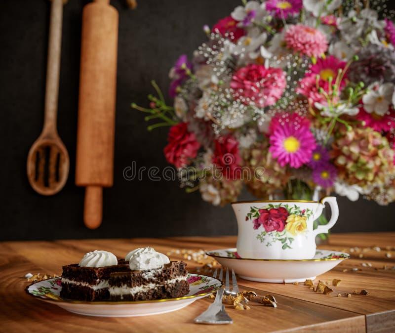 Κινηματογράφηση σε πρώτο πλάνο του φλυτζανιού του τσαγιού με το κέικ και της ανθοδέσμης λουλουδιών στην ξύλινη επιτραπέζια στενή  στοκ εικόνες