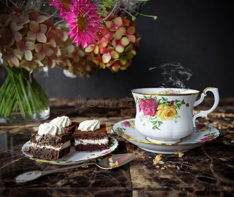 Κινηματογράφηση σε πρώτο πλάνο του φλυτζανιού του τσαγιού με το κέικ και της ανθοδέσμης λουλουδιών στην ξύλινη επιτραπέζια στενή  στοκ φωτογραφία