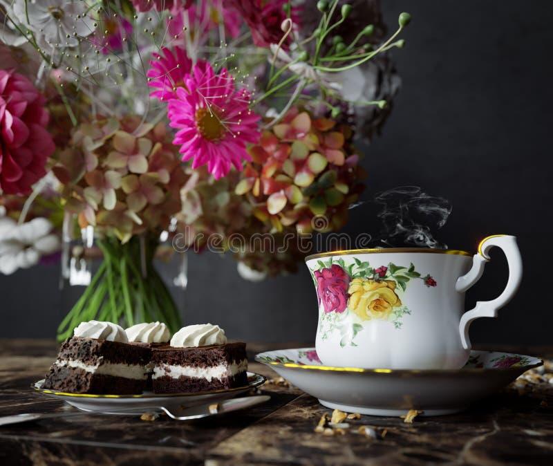 Κινηματογράφηση σε πρώτο πλάνο του φλυτζανιού του τσαγιού με το κέικ και της ανθοδέσμης λουλουδιών στην ξύλινη επιτραπέζια στενή  στοκ εικόνα με δικαίωμα ελεύθερης χρήσης