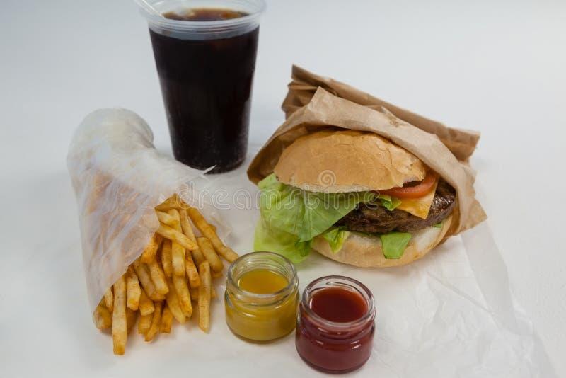 Κινηματογράφηση σε πρώτο πλάνο του χάμπουργκερ, των τηγανιτών πατατών, της σάλτσας και του κρύου ποτού στοκ φωτογραφίες με δικαίωμα ελεύθερης χρήσης