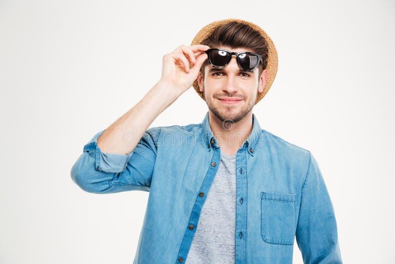 Κινηματογράφηση σε πρώτο πλάνο του χαμογελώντας όμορφου νεαρού άνδρα στο καπέλο και τα γυαλιά ηλίου στοκ εικόνα
