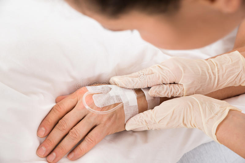 Κινηματογράφηση σε πρώτο πλάνο του χεριού ενός IV σταλαγματιάς ασθενή στοκ εικόνες