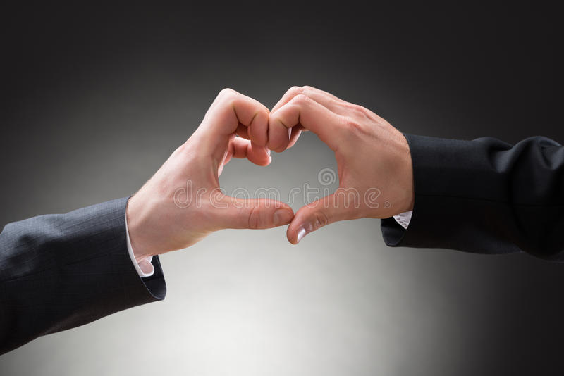 Κινηματογράφηση σε πρώτο πλάνο του χεριού ομοφυλόφιλων που κάνει heartshape στοκ εικόνες