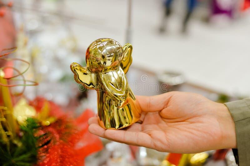 Κινηματογράφηση σε πρώτο πλάνο του χεριού που κρατά το χρυσό άγγελο Χριστουγέννων στοκ εικόνες με δικαίωμα ελεύθερης χρήσης
