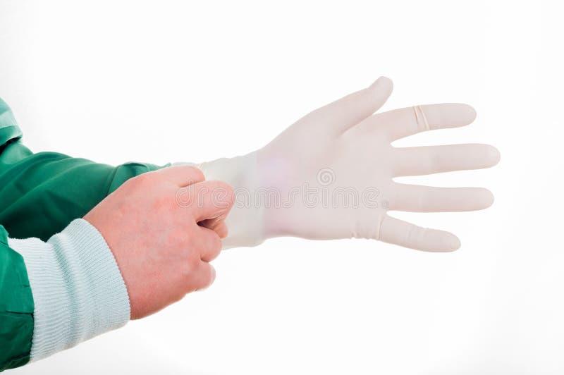 Κινηματογράφηση σε πρώτο πλάνο των αρσενικών χεριών γιατρών ` s που βάζουν στο αποστειρωμένο χειρουργικό γάντι στοκ εικόνες