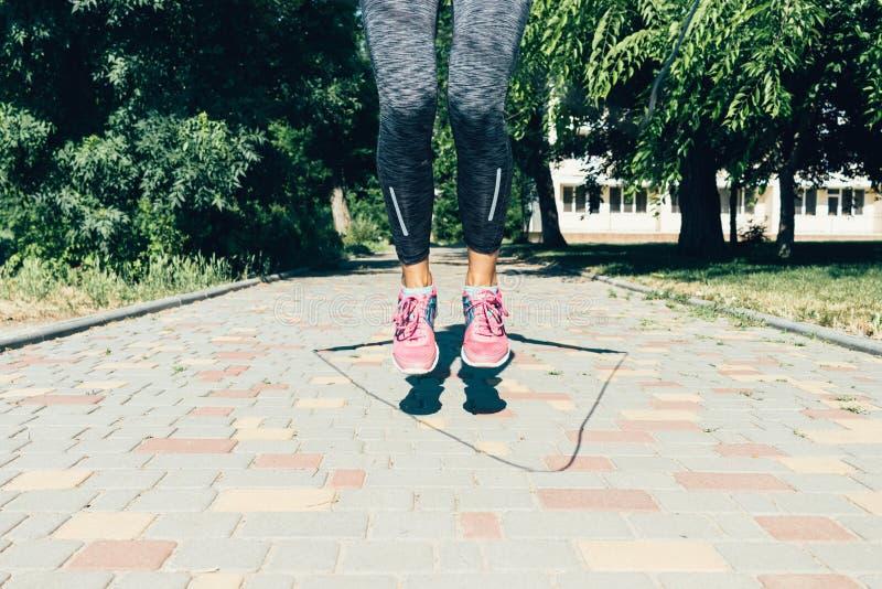 Κινηματογράφηση σε πρώτο πλάνο των θηλυκών ποδιών στα πάνινα παπούτσια που πηδούν το σχοινί στο θερινό outdo στοκ εικόνα