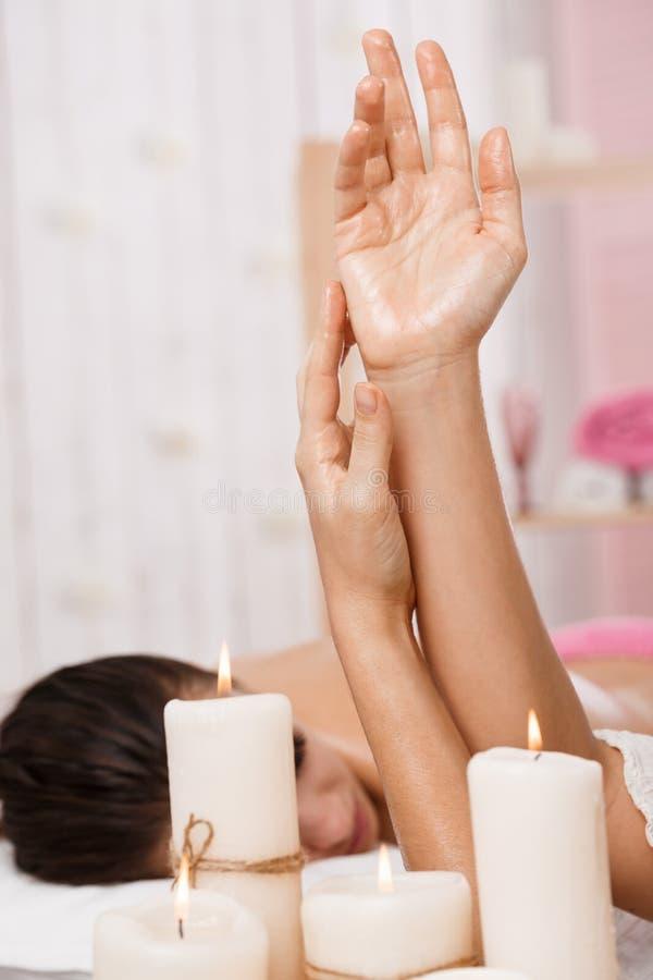 Κινηματογράφηση σε πρώτο πλάνο των θηλυκών χεριών που εφαρμόζουν το ενυδατικό λοσιόν πριν από το μασάζ στοκ φωτογραφία