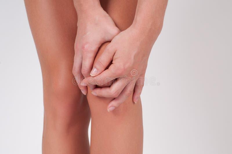 Κινηματογράφηση σε πρώτο πλάνο των θηλυκών χεριών σχετικά με το πόδι, που αισθάνεται τον πόνο στο γόνατο στοκ εικόνες με δικαίωμα ελεύθερης χρήσης