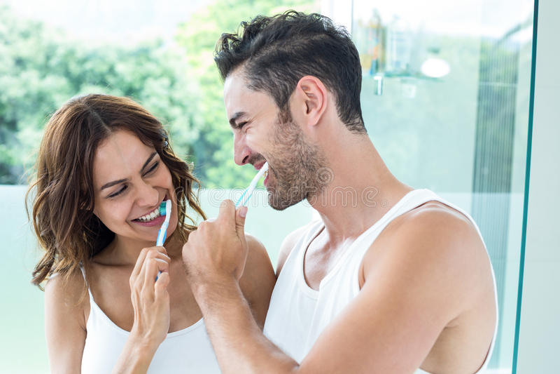 Κινηματογράφηση σε πρώτο πλάνο των νέων δοντιών βουρτσίσματος ζευγών στοκ φωτογραφία