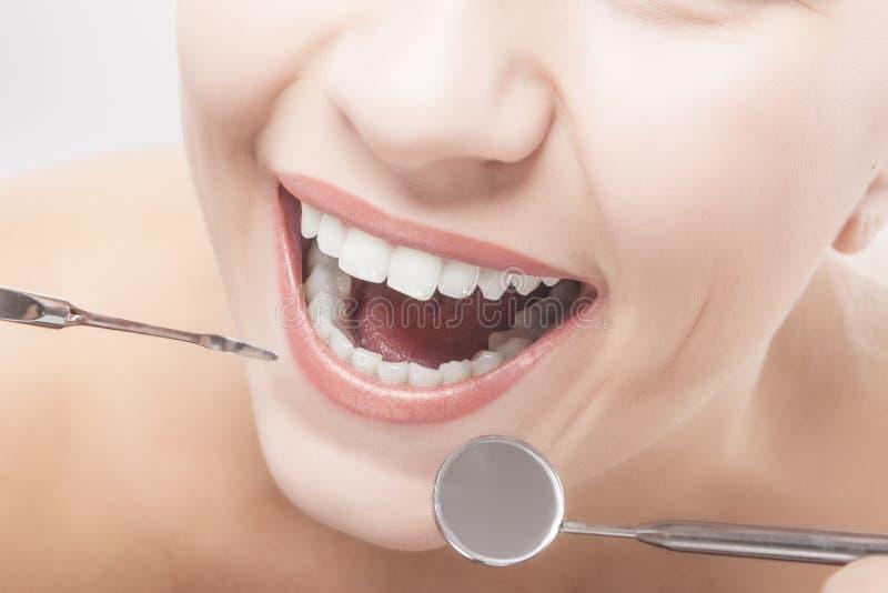 Κινηματογράφηση σε πρώτο πλάνο των δοντιών γυναικών με τα οδοντικά εργαλεία στοκ φωτογραφία