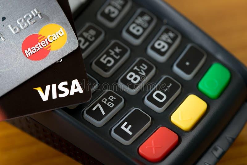 Κινηματογράφηση σε πρώτο πλάνο των πιστωτικών καρτών ΘΕΩΡΗΣΕΩΝ στη μηχανή πιστωτικών καρτών στοκ εικόνα