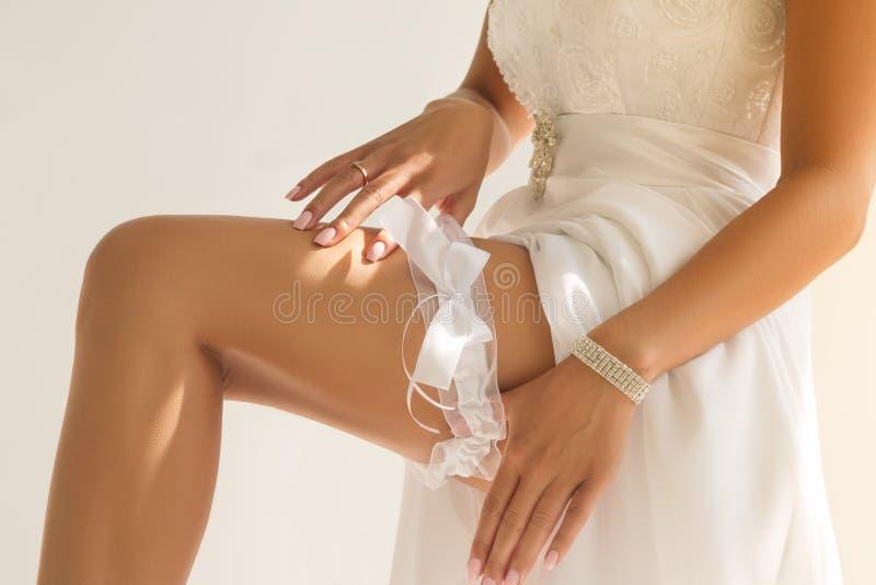 Κινηματογράφηση σε πρώτο πλάνο των χεριών της νύφης που βάζουν garter στοκ φωτογραφία με δικαίωμα ελεύθερης χρήσης