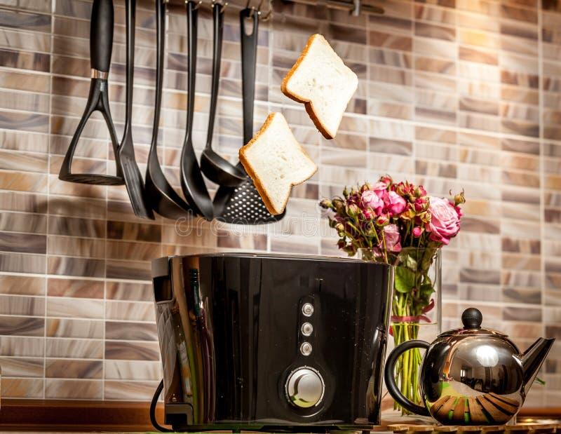 Κινηματογράφηση σε πρώτο πλάνο δύο φετών του ψωμιού που σκάουν από τη φρυγανιέρα στην κουζίνα στοκ εικόνες