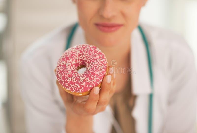 Κινηματογράφηση σε πρώτο πλάνο doughnut εκμετάλλευσης γυναικών γιατρών στοκ εικόνες