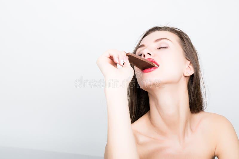 Κινηματογράφηση σε πρώτο πλάνο portret της όμορφης προκλητικής γυναίκας με τα κόκκινα χείλια που τρώει τη σοκολάτα στοκ φωτογραφίες με δικαίωμα ελεύθερης χρήσης