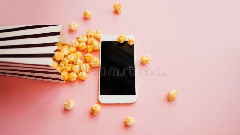 Κινηματογράφοι και σειρές από τη συνδρομή, έννοια το smartphone βρίσκεται δίπλα σε ένα γραπτό ριγωτό κιβώτιο papper popcorn στοκ φωτογραφία με δικαίωμα ελεύθερης χρήσης