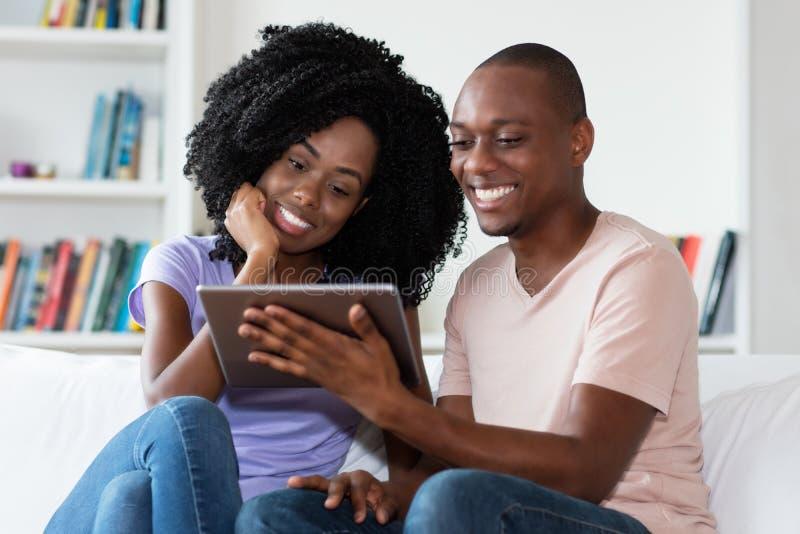 Κινηματογράφος προσοχής ζευγών αφροαμερικάνων με τον υπολογιστή ταμπλετών στοκ εικόνες