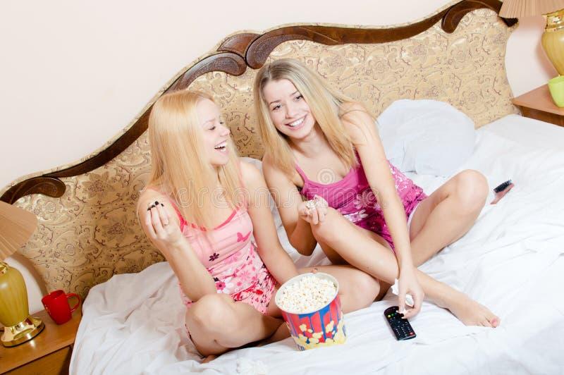 Κινηματογράφος στο σπίτι: 2 λατρευτές ελκυστικές αρκετά νέες ξανθές γυναίκες που έχουν τη συνεδρίαση διασκέδασης στο κρεβάτι με p στοκ εικόνες