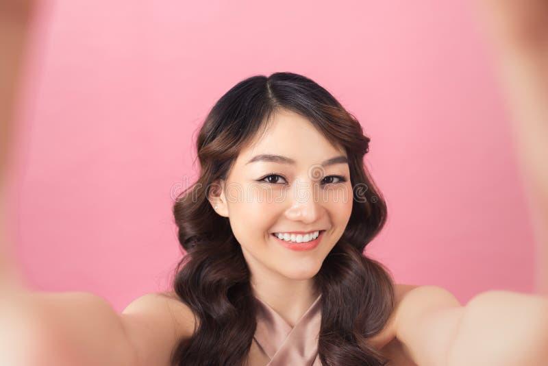 Κινηματογραφικό πορτραίτο όμορφης γυναίκας που χαμογελάει με λευκά δόντια και φτιάχνει selfie, φωτογραφίζοντας τον εαυτό της πάνω στοκ φωτογραφίες με δικαίωμα ελεύθερης χρήσης