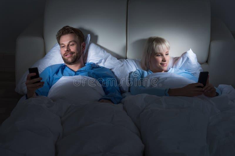 Κινητά τηλέφωνα εκμετάλλευσης ζεύγους στην κρεβατοκάμαρα στοκ φωτογραφίες