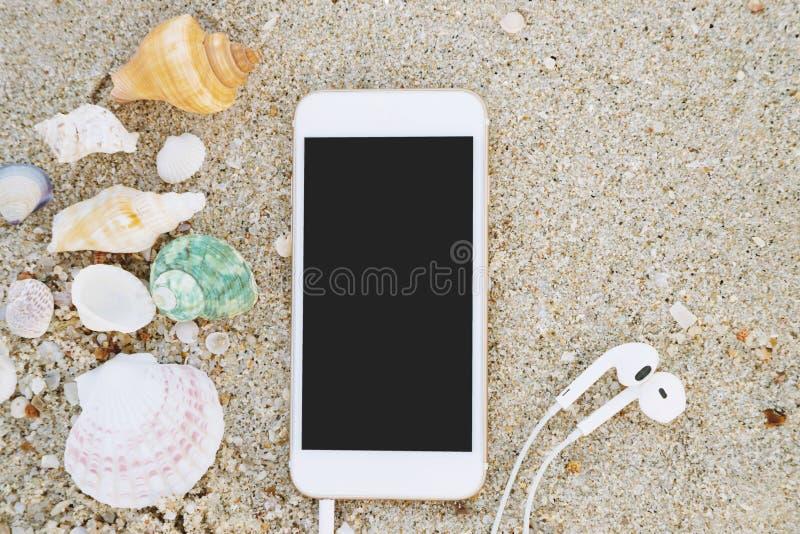 Κινητό έξυπνο τηλέφωνο με την οθόνη κενή και ακουστικό που βρίσκεται στη θάλασσα παραλιών στοκ εικόνες