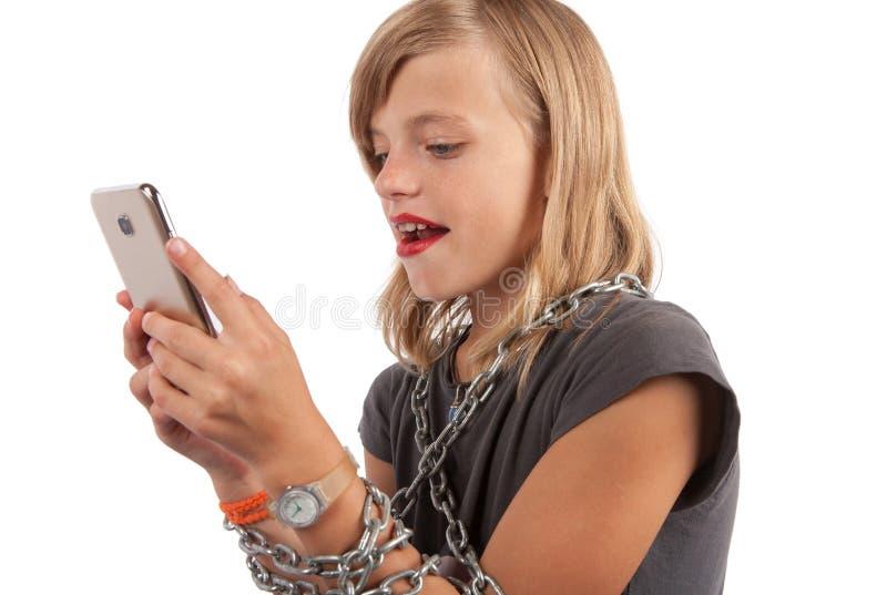 Κινητό εθισμένο παιδί με το smaptphone και την αλυσίδα στοκ φωτογραφία