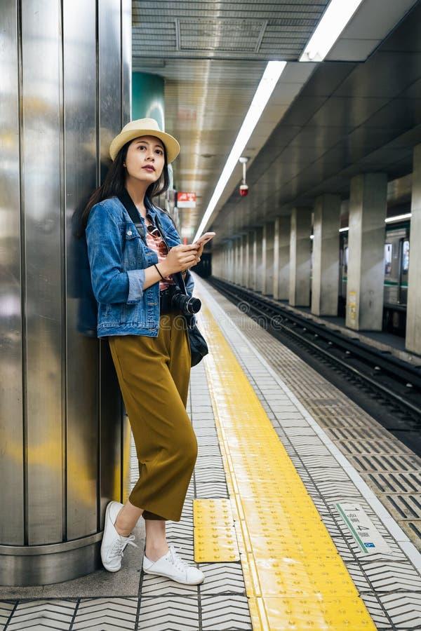 Κινητό τηλέφωνο εκμετάλλευσης τουριστών που στέκεται στην πλατφόρμα στο σταθμό μετρό που περιμένει το τραίνο νέος γυναικείος ταξι στοκ φωτογραφίες με δικαίωμα ελεύθερης χρήσης