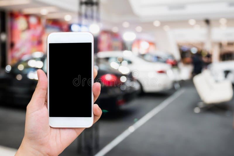 Κινητό τηλέφωνο λαβής χεριών με την αίθουσα εκθέσεως αυτοκινήτων στοκ εικόνα με δικαίωμα ελεύθερης χρήσης