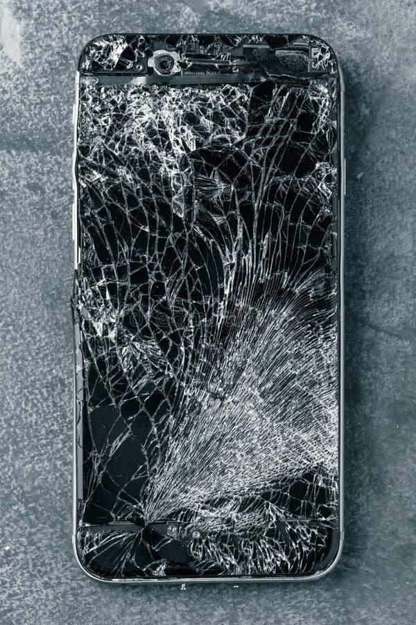 Κινητό τηλέφωνο με τη σπασμένη οθόνη επαφής στο γκρίζο υπόβαθρο στοκ εικόνες