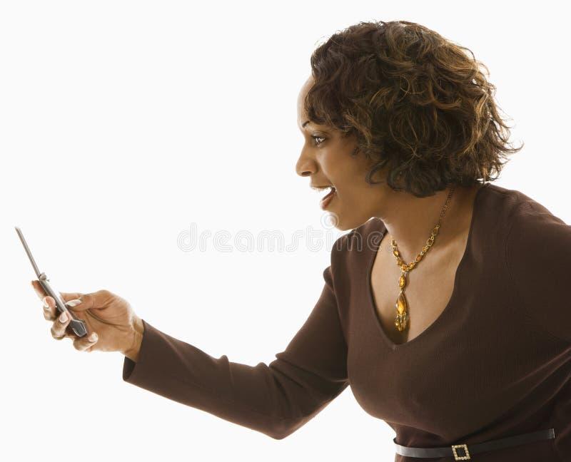κινητό τηλέφωνο που φαίνεται γυναίκα στοκ εικόνες με δικαίωμα ελεύθερης χρήσης