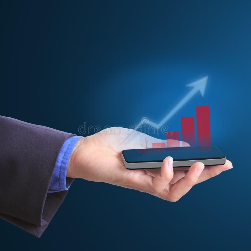 Κινητό τηλέφωνο λαβής επιχειρηματιών για την ανάπτυξη της επιχείρησης στοκ φωτογραφία